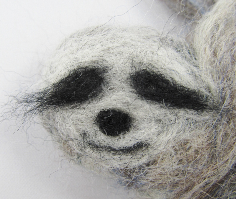 Needle a small amount of natural wool to the face. Use a small amount of black wool for the eye markings and mouth. For the nose, roll a bit of wool into a ball and needle it in place.
