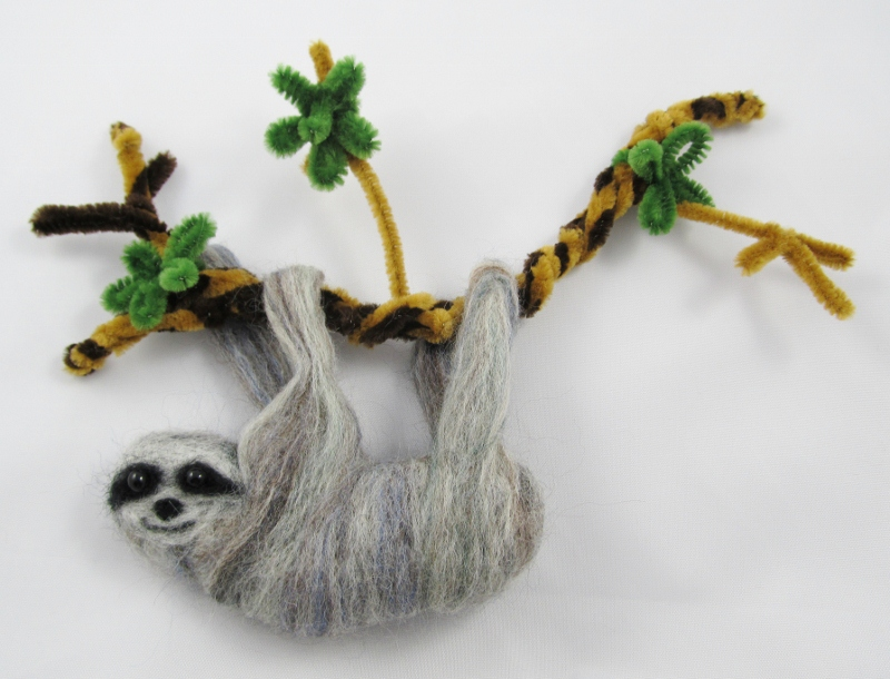 Sew the sloth to the branch through the paws. Hang by the branch on a wall.